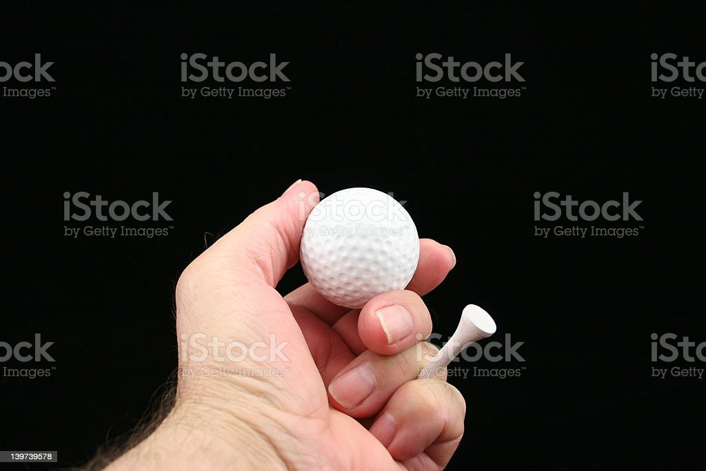 Golf ball & tee in hand. royalty-free stock photo