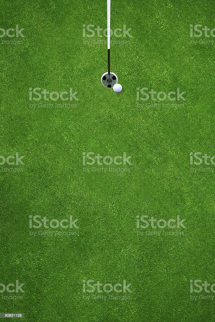 A golf ball teetering on the edge of the hole stock photo