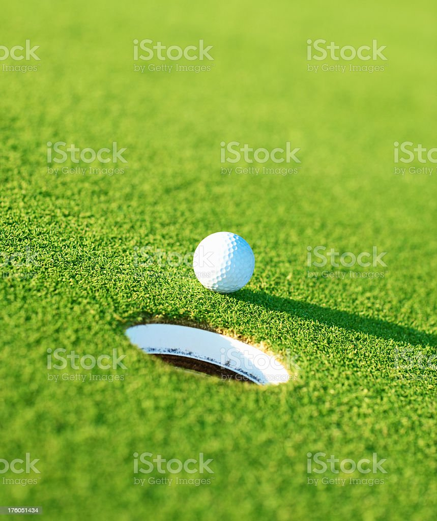 Golf ball with hole on green royalty-free stock photo