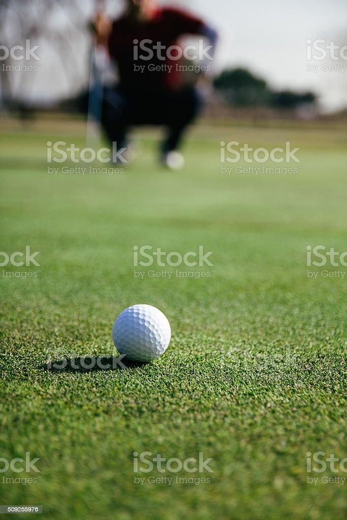Golf ball with unfocused golfer crouched in the background stock photo