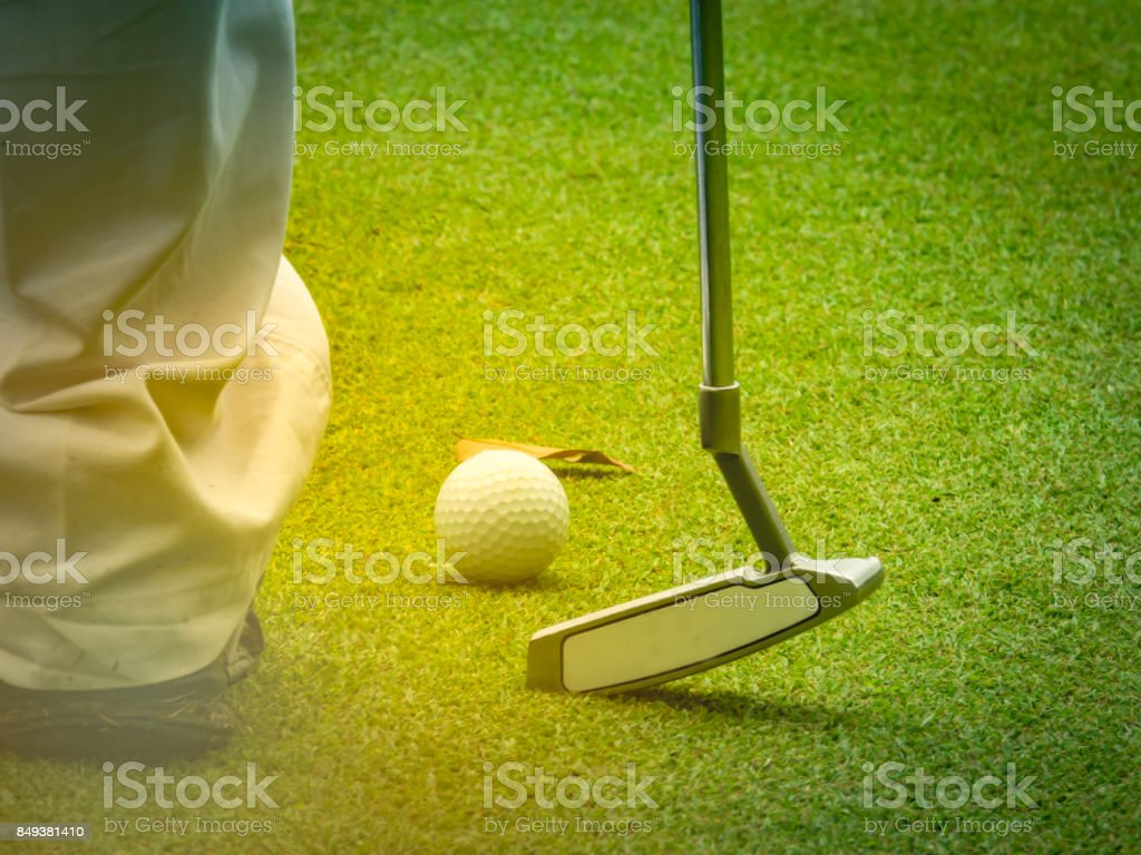 Golf balls and golf clubs placed on Green Golf and Blurred golfer...