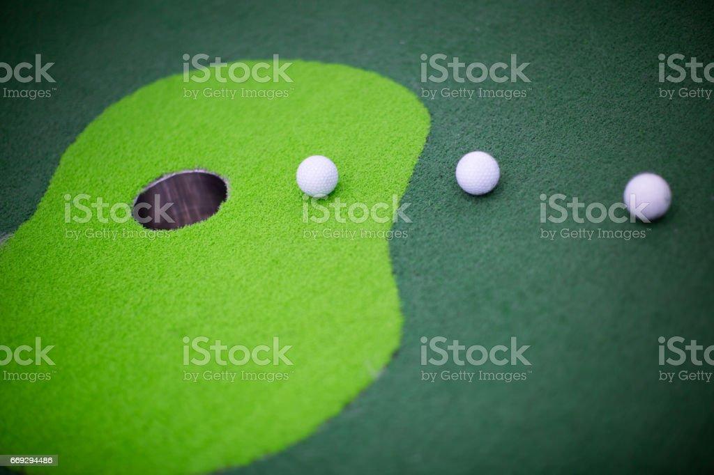 Golf Balls Curving Towards Hole. Goal. Win. stock photo
