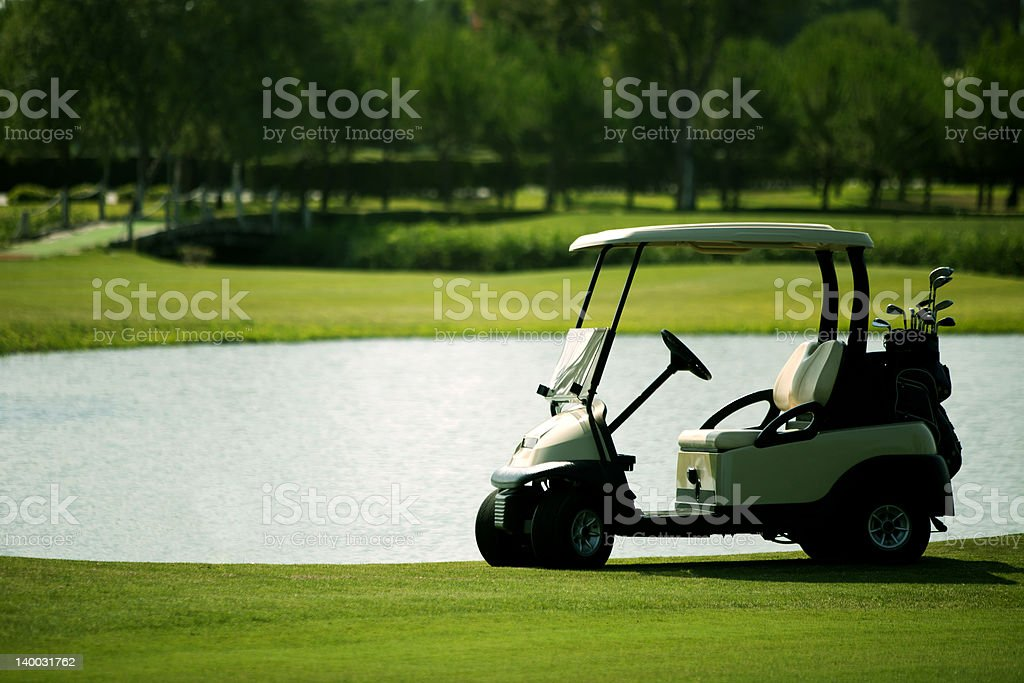 A golf cart on the green near the water royalty-free stock photo