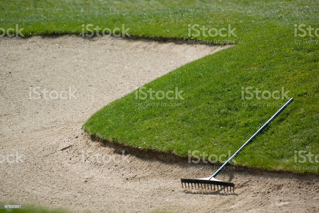 Golf club bunker with rake and sand stock photo