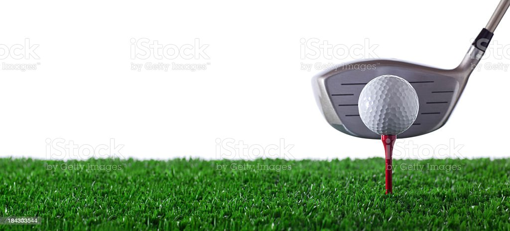 Golf club next to golf ball on red tee on grass stock photo