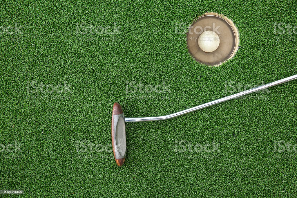 Golf club on green grass with golf ball in hole stock photo