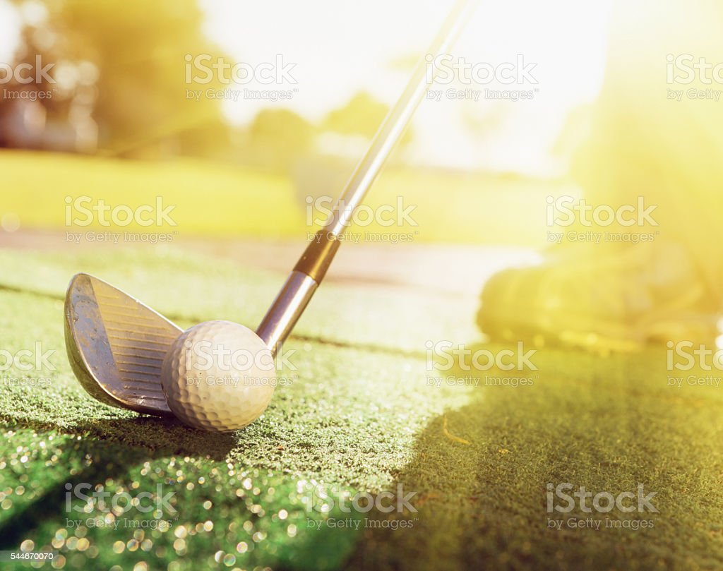Golf club  ready to hit ball on sunny golf course stock photo