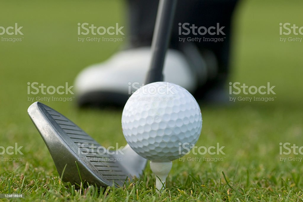 Golf club with ball and shoe in the background royalty-free stock photo