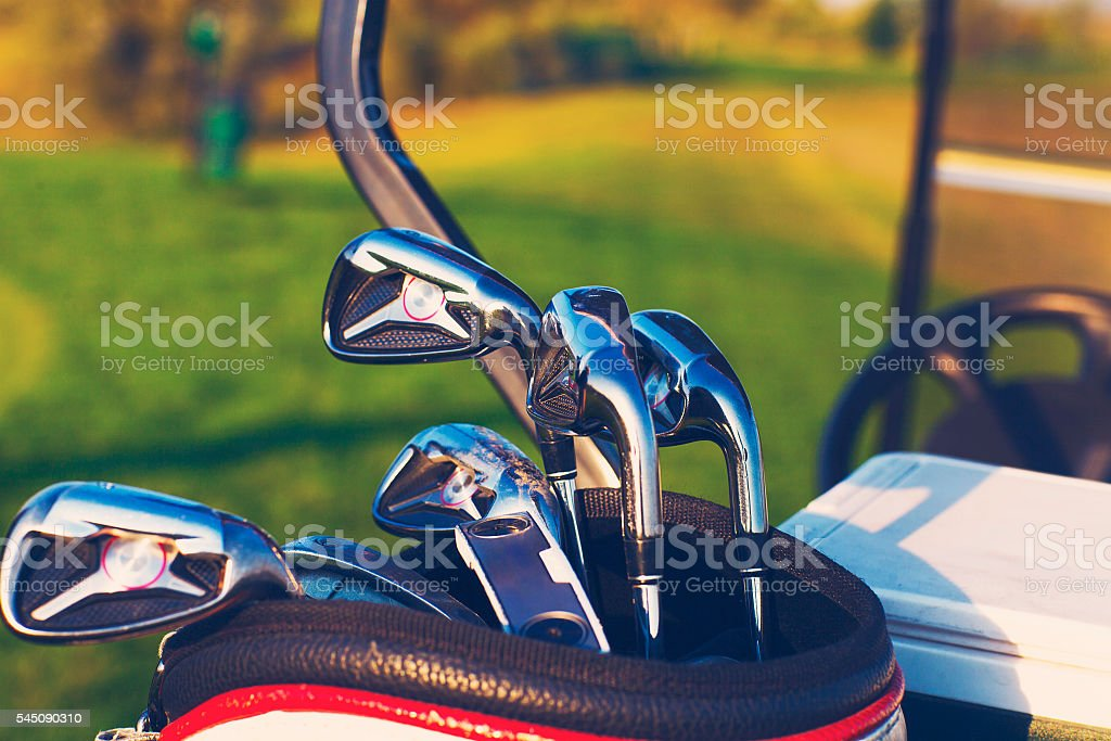 Golf clubs drivers over green field background stock photo
