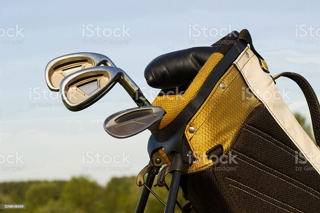 Three golf clubs in yellow golf bag. Nature background.