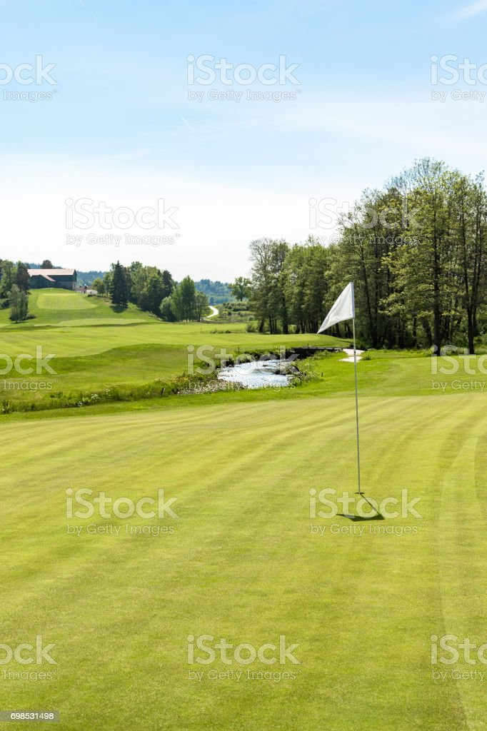 Golf course. Hole with a white flag on a sunny day stock photo