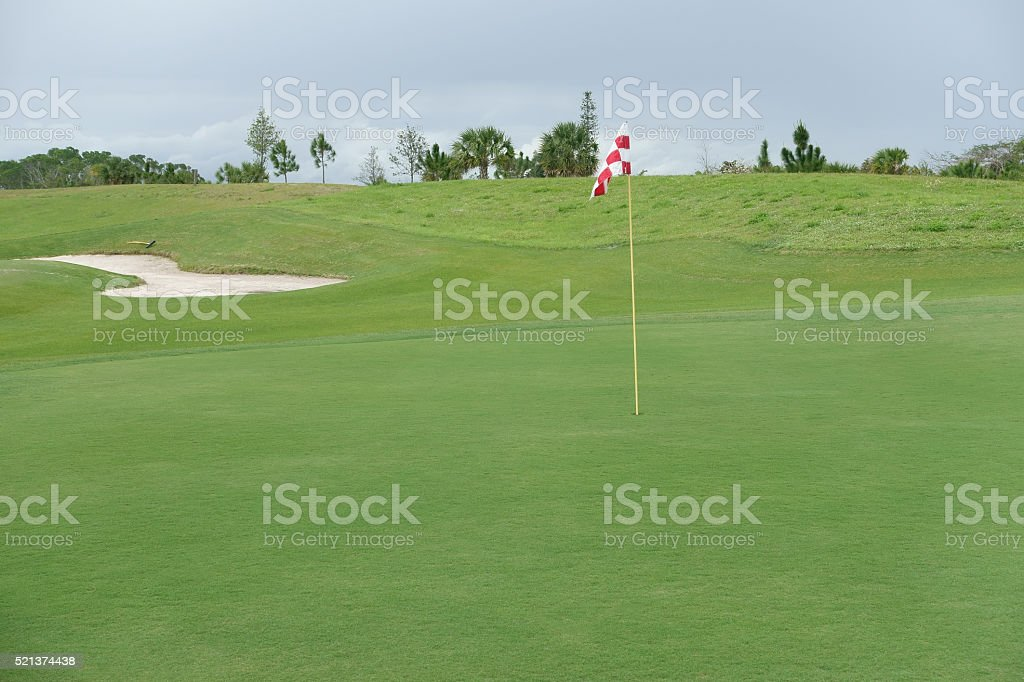 Golf course putting green with flag in hole stock photo