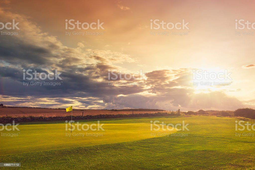 Golf course putting green with sunbeam - UK stock photo