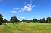 Golf course with green grass, trees, sandy bunkers, hazards, sky