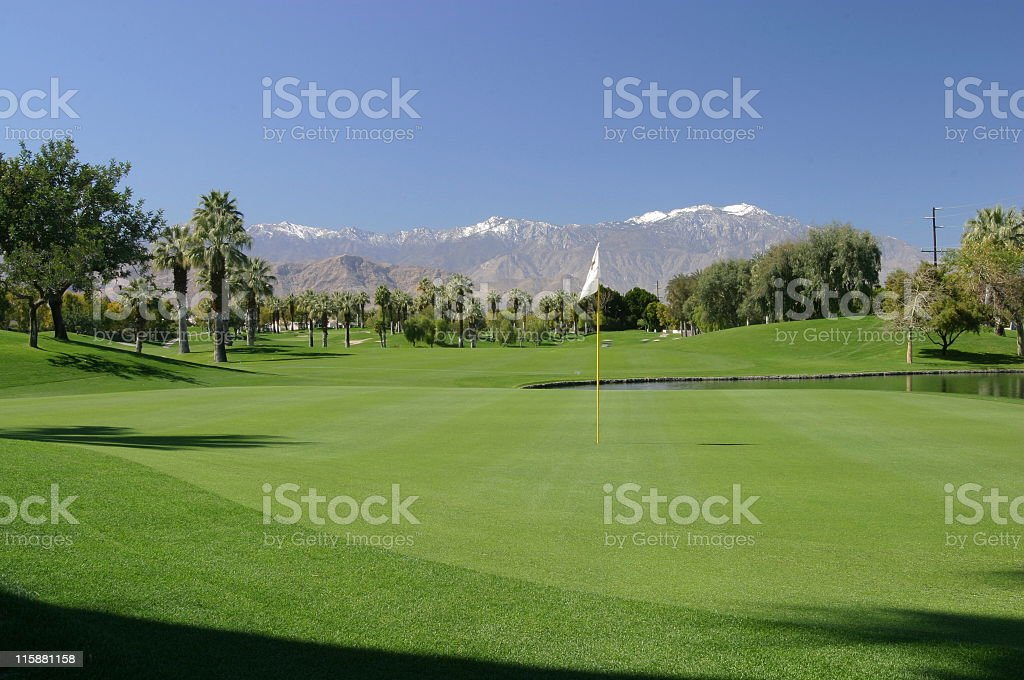 Golf course with snow on mountains stock photo