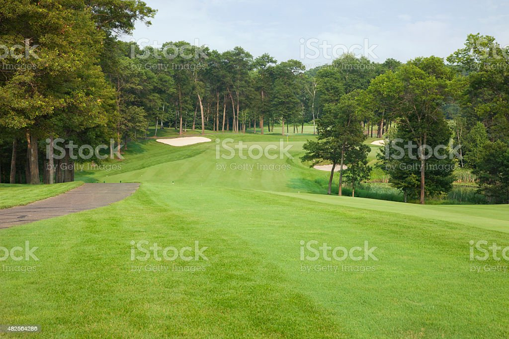 Golf fairway leading to green and sand traps stock photo