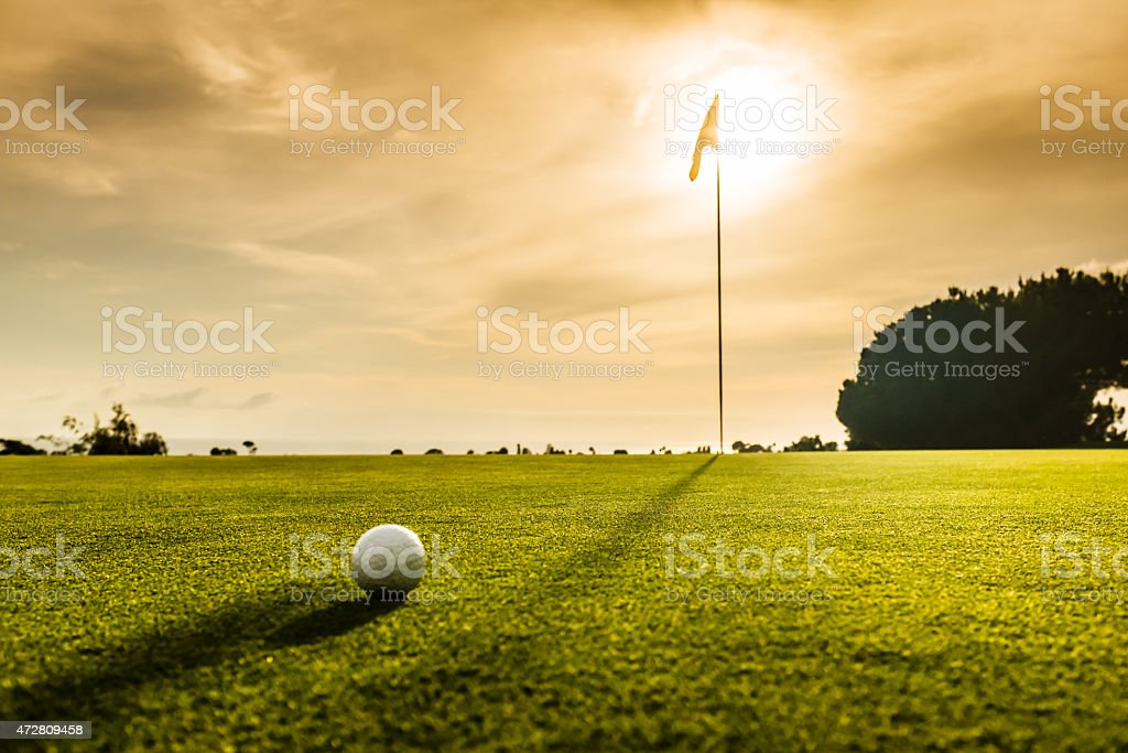 Golf Flag and Ball At Sunset stock photo