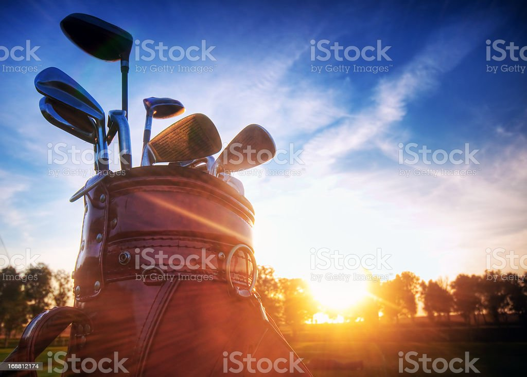 Golf gear, clubs at sunset stock photo