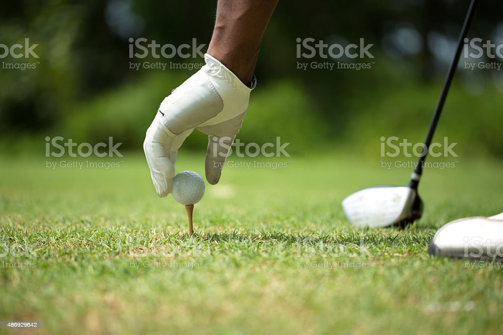 African American man placing the golf ball.