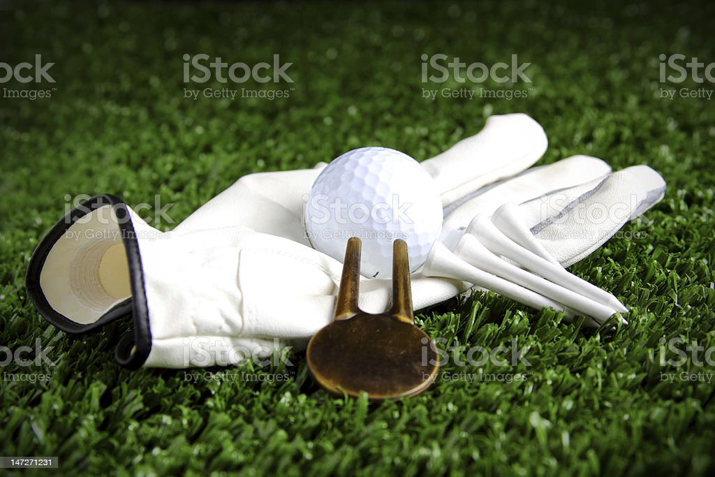 Golf glove with ball tees and pitch repairer stock photo