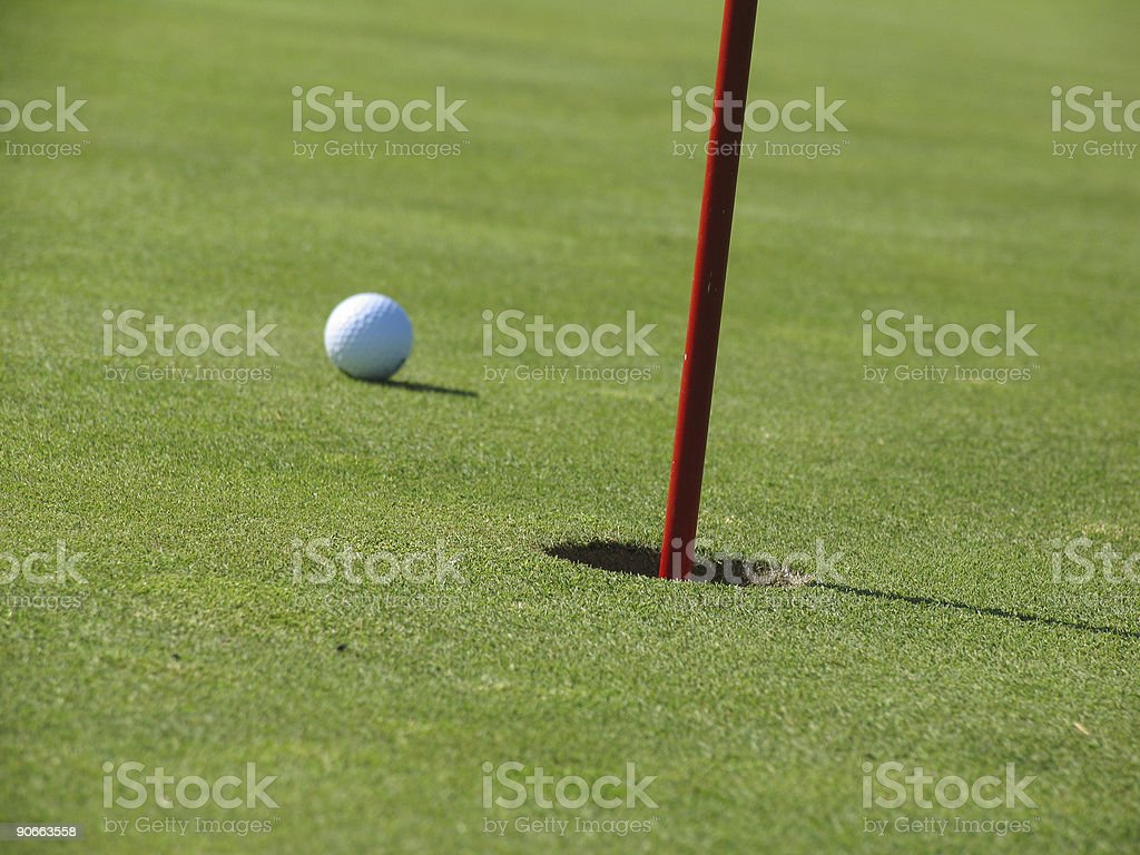 Golf Green and Ball Next to Hole stock photo