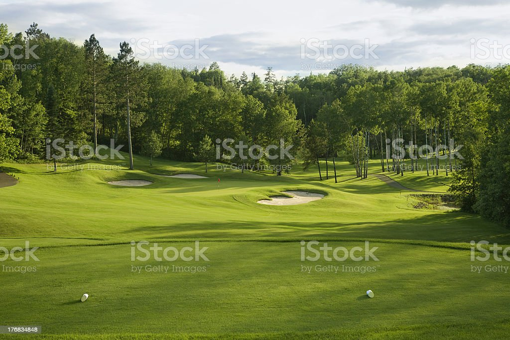 Golf green and tee box in late afternoon sunlight stock photo