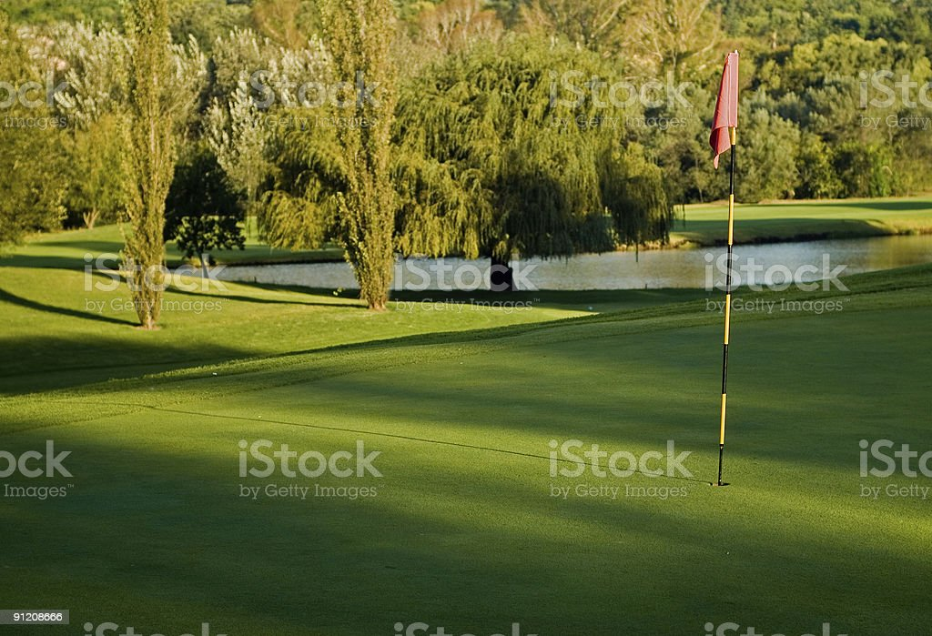 Golf green, flag and water hazard royalty-free stock photo