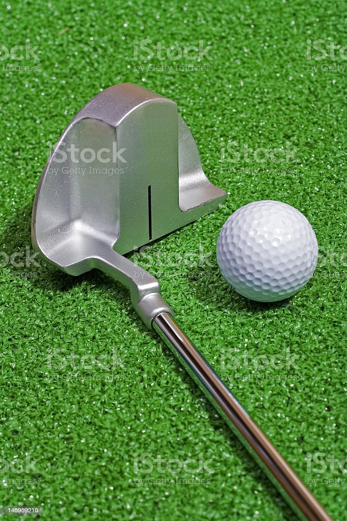 A putter rests beside a golf ball on the green.