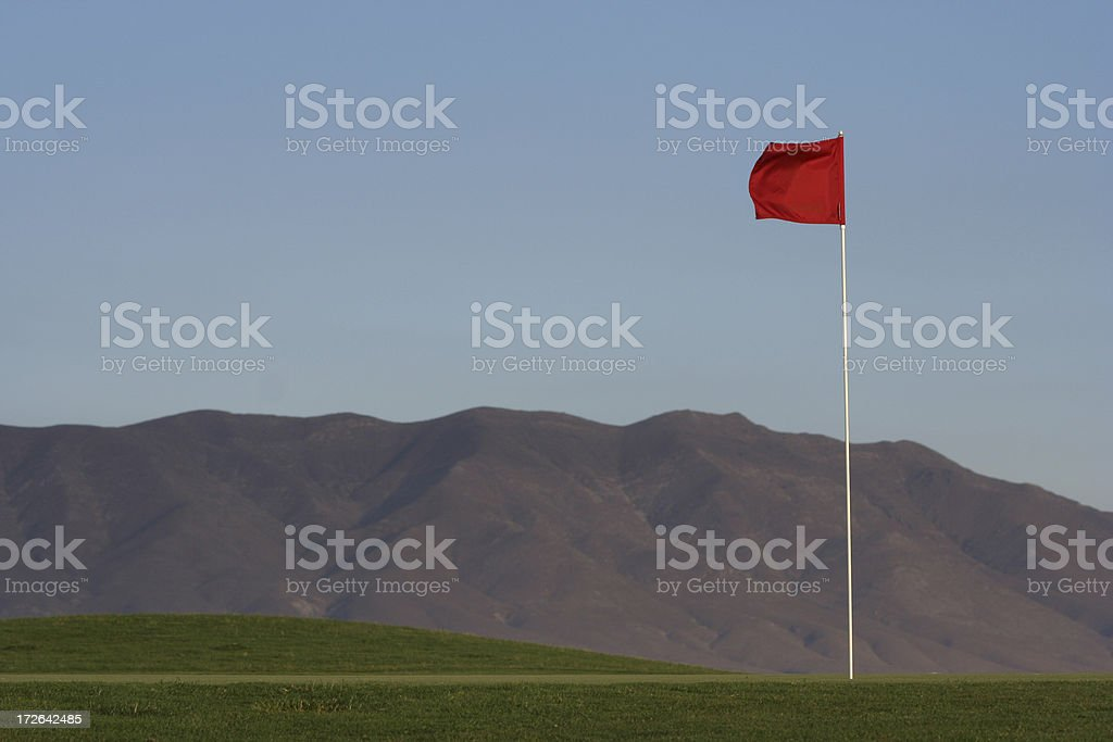 Golf Green, Pin with red flag, and Mountain Ridge royalty-free stock photo