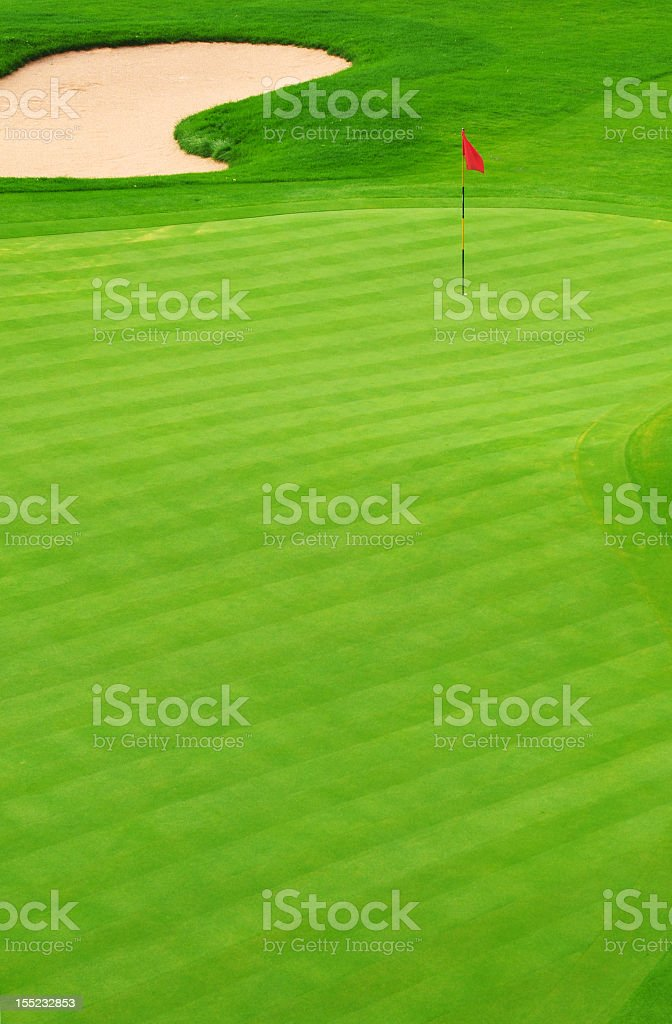 Golf green with sand bunker and red flag marking hole stock photo