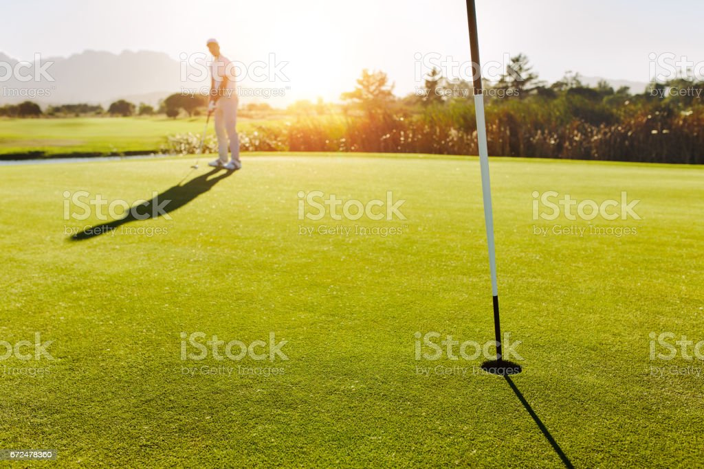Golf hole and flag in the green field with player in background stock photo