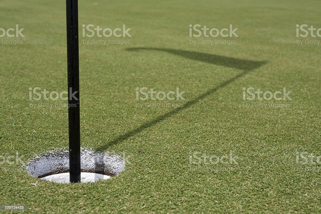 Golf Hole and the Shadow of Flag royalty-free stock photo
