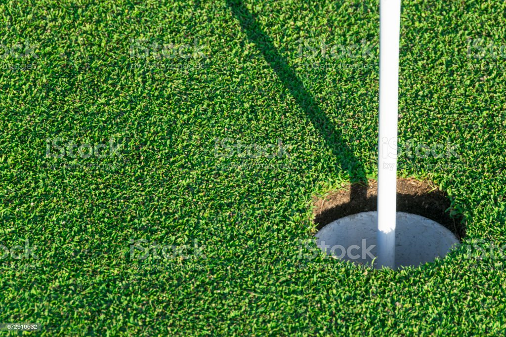 Golf hole on green grass of golf course. View of golf hole on green field. stock photo