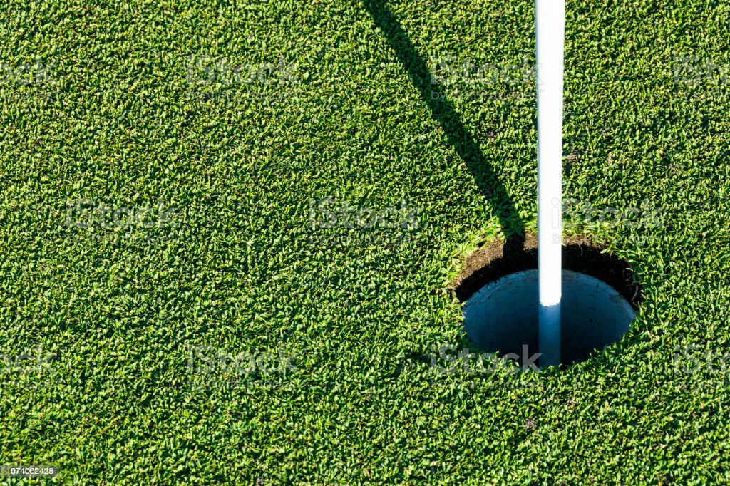 Golf hole on green grass of golf course. View of golf hole on green...