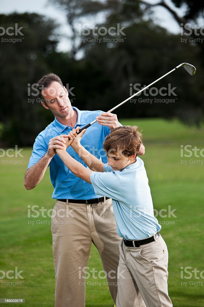 Golf instructor adjusting boy's grip stock photo