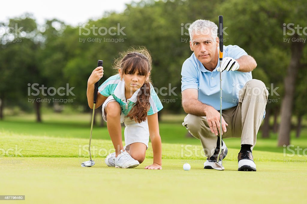Golf instructor teaching technique to little girl stock photo