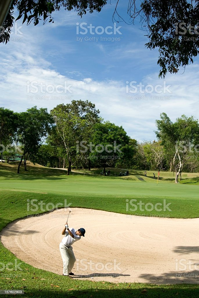 A golf player hitting the ball from the sand royalty-free stock photo