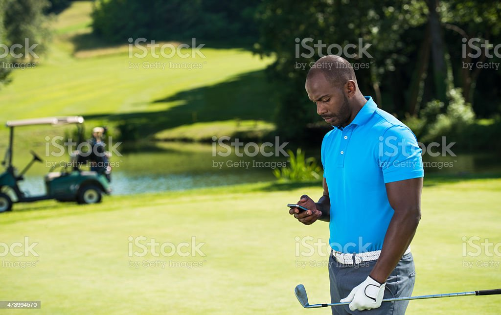 Golf player looking at his smart phone on the course stock photo