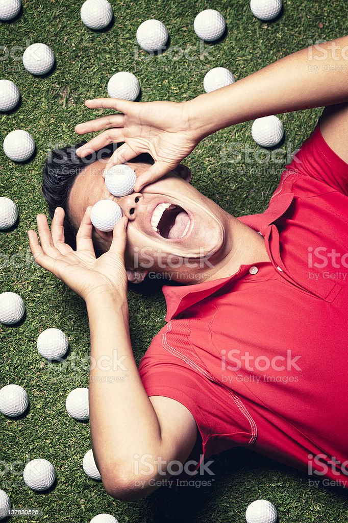 Golf player on floor with balls infront of eyes. stock photo