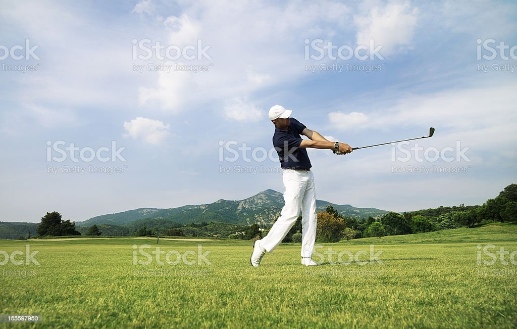 Golf Player. Perfect Swing on the Course. Moody Sky. royalty-free stock photo