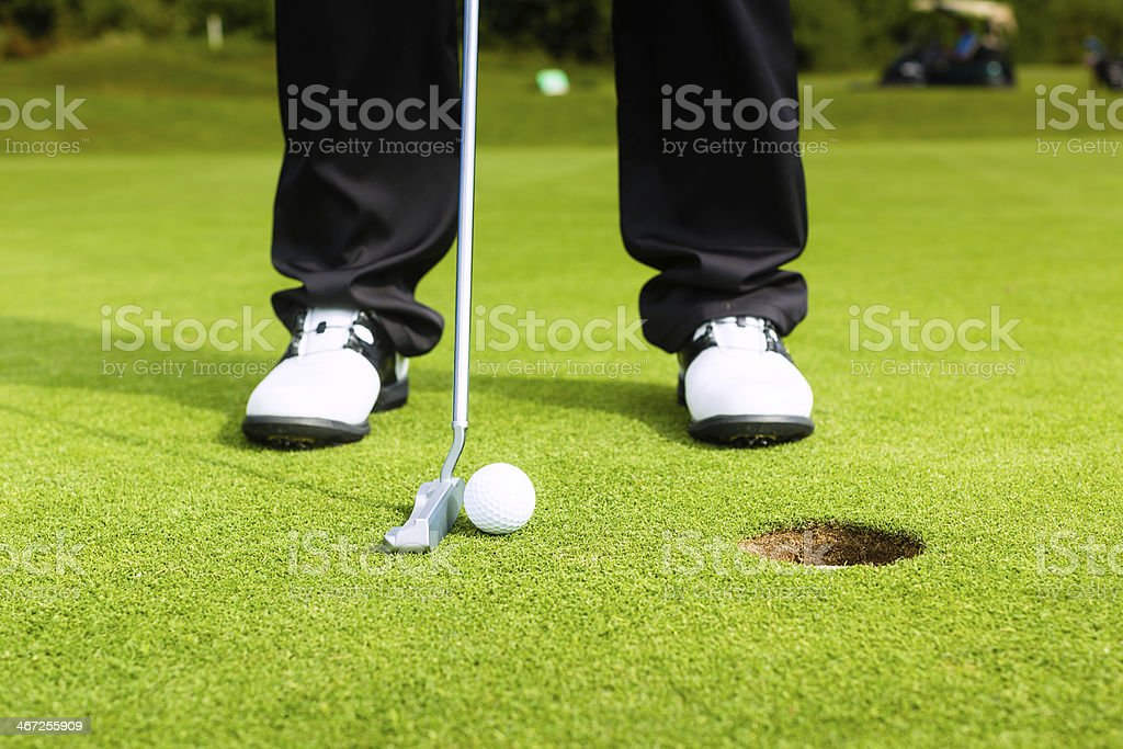 Golf player putting ball in hole stock photo