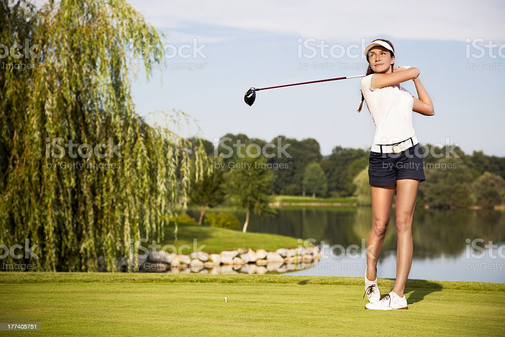 A golf player teeing off on a sunny day stock photo