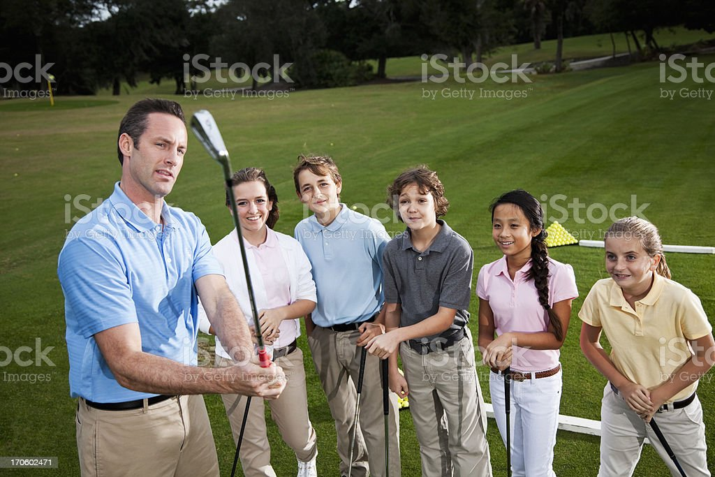 Golf pro with group of children on driving range stock photo