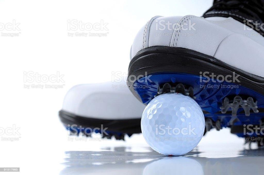 Golf shoes standing on a golf ball stock photo