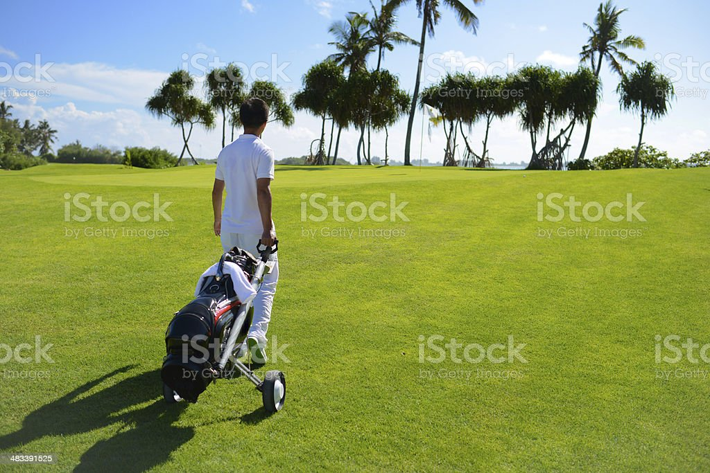 A man is walking to golf green with golf cart