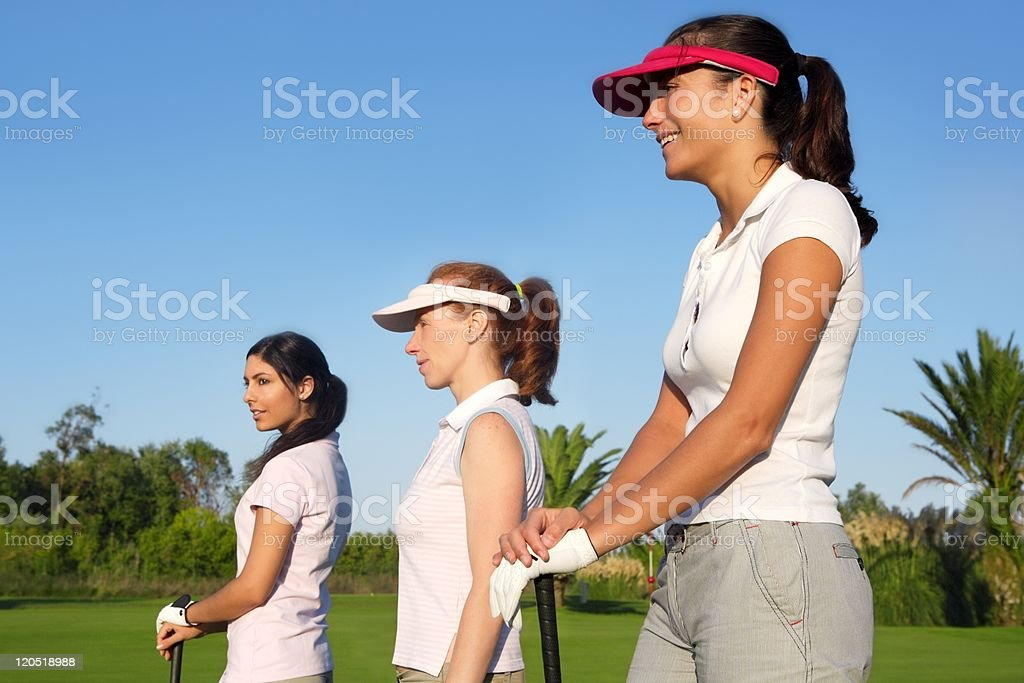 Golf three woman in a row green grass course stock photo