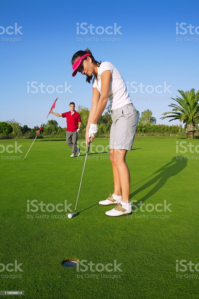 golf woman player green putting hole golfball stock photo