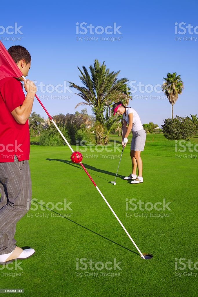 golf woman putting ball and man holds flag royalty-free stock photo