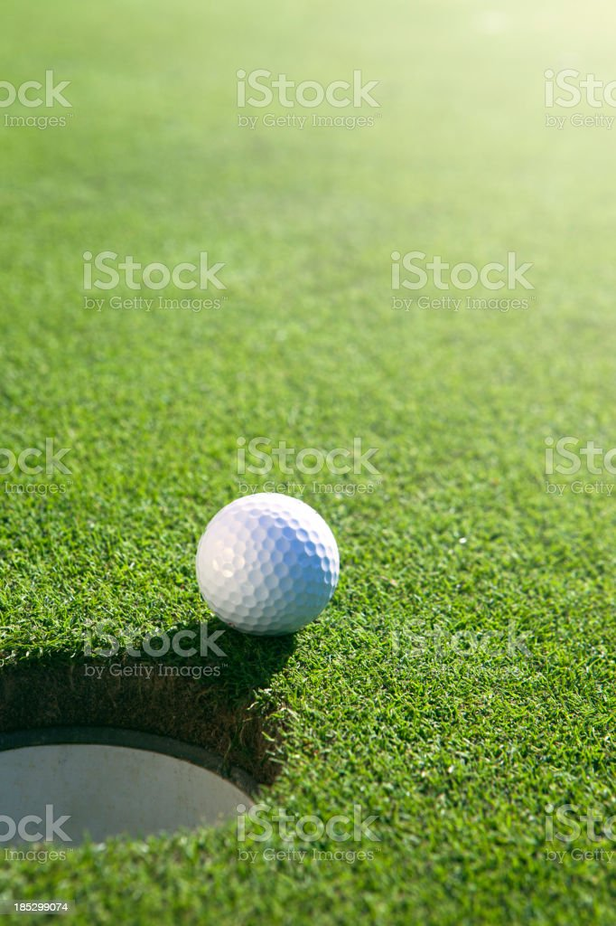 Golfball close to hole royalty-free stock photo