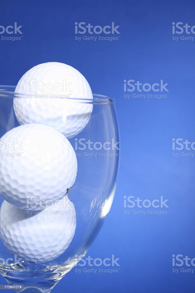 Golfball in wineglass (blue) royalty-free stock photo